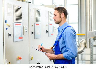 worker in blue work clothes in front of control cabinet