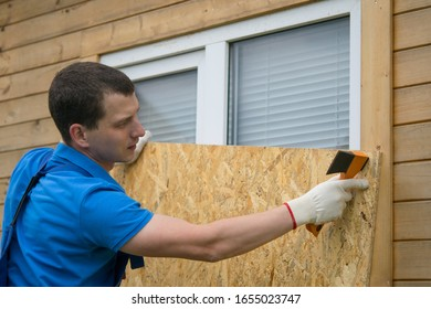worker, boarded up the window of the house with a protective shield made of wood, from thieves, when moving to another address, close-up