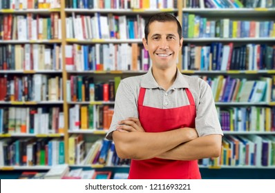 a worker at a bookstore smiling and looking at camera