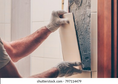 Worker breaks the remnants of tiles off the wall