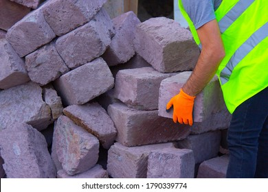Worker build a dry stone wall on a construction site.