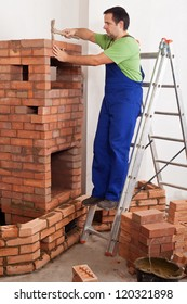 Worker building masonry heater - finishing the firebox with chamotte bricks