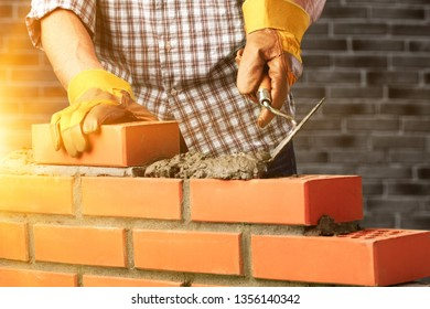 Worker builds a brick wall