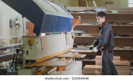 Worker carpenter handles wooden furniture parts on the machine on the factory