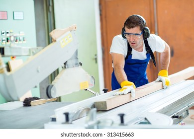 worker in a carpenter's workshop using saw machine