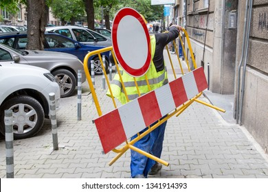 A worker carry on forbidden traffic sign through the street.