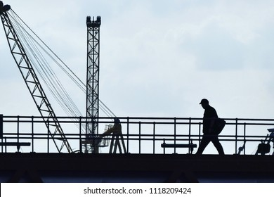 A worker carrying a bag heading to work passing cranes and railings. He is in silhouette against a blue hint cloudy sky