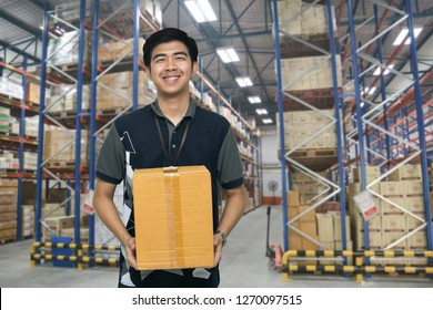 Worker carrying box in the warehouse, Asian delivery man carrying boxes in the distribution warehouse