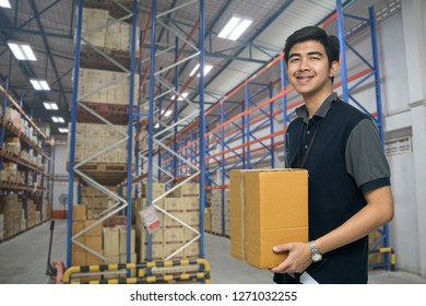 Worker carrying box in the warehouse (ฺBlur background) , Asian delivery man carrying boxes in the distribution warehouse (ฺBlur background)