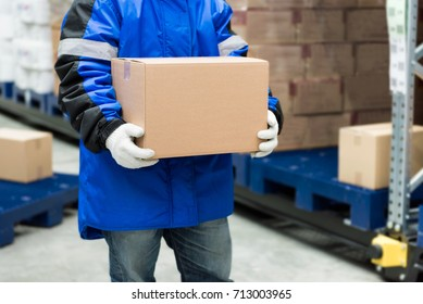 Worker carrying a goods box in a large frozen warehouse.Export-Import Logistics system concept