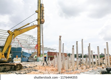 Worker carrying out ground piling work at construction site with heavy machinery
