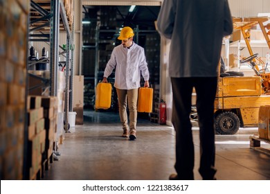 Worker carrying water tanks. Warehouse interior.