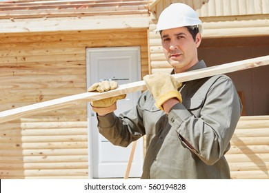 Worker carrying wood at construction site during building construction