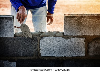 Worker is cementing bricks with cement for brick wall