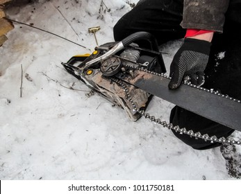 The worker changes and adjusts the chain on the chainsaw, preparing it for cutting down trees and sawing firewood in winter on snow