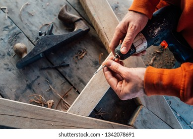 a worker changes a drill in a screwdriver, against the background of a wooden table with tools
