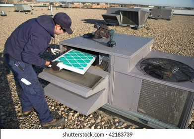 Worker changing a roof top air exchange units filter.