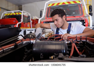worker charging car battery with a set of jumper cables