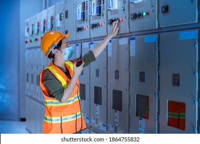 Worker checking and inspecting at MDB panel ,working with electric switchboard to check range of voltage in Main Distribution water to support station,wearing mask to protect virus and pollution.