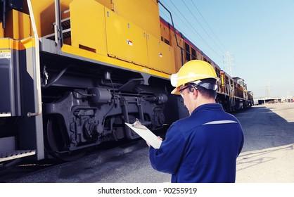 worker checking on train machine