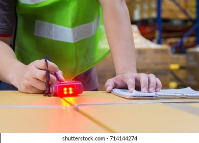 A worker checking stock by RFID scanning in a warehouse.He use a pen touch on handheld scanner. A device show red light.