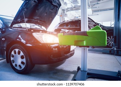Worker checks and adjusts the headlights of a car's lighting system. Auto repair service.