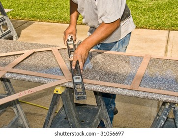 A worker checks the size of a granite slab for use in a suburban home kitchen remodel