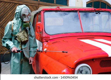 A worker in a chemical protection suit and gas mask conducts decontamination of a vehicle that is in the zone of strong radiation at the Chernobyl nuclear power plant.