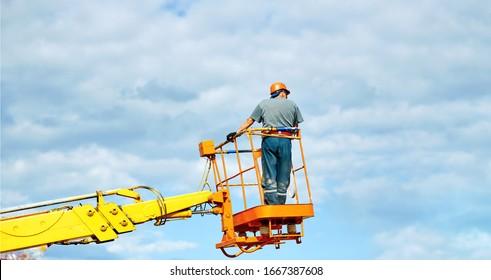 高さのチェリーピッカーのバケツで働く人は、ハードハットと安全ハーネスを身に着けている。青い空に高さの建設作業者。移動式クレーンバケットに立ち上がり、道路の配線を修理する電気技師