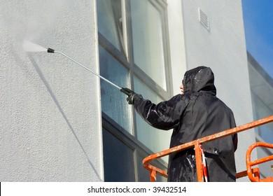 worker in cherry-picker washing a wall