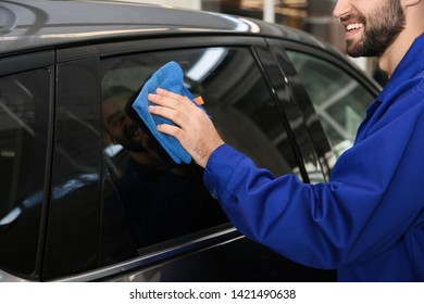 Worker cleaning automobile window with rag at car wash, closeup