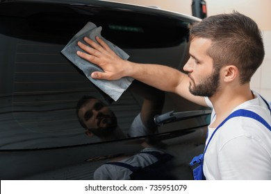 Worker cleaning car window after tinting