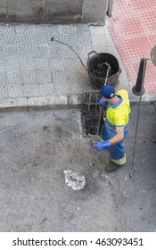 WORKER CLEANING  A DRAIN