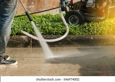 Worker cleaning driveway with gasoline high pressure washer splashing the dirt,high angle view. High pressure cleaning,lower body.Professional cleaning services.
