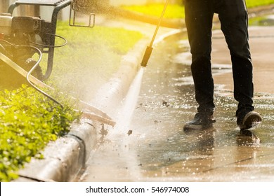 Worker cleaning driveway with gasoline high pressure washer splashing the dirt,backlighting and low angle view.High pressure cleaning,lower body.