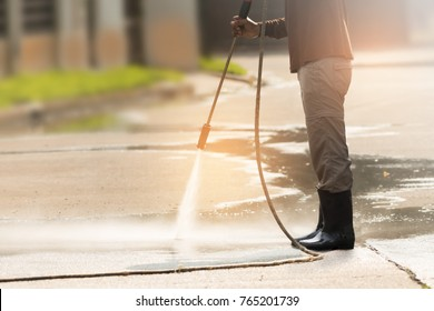 Worker cleaning driveway with gasoline high pressure washer splashing the dirt with backlighting, waist level angle view . High pressure cleaning,lower body.Professional cleaning services.