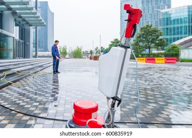 Worker cleaning floor with high pressure washer