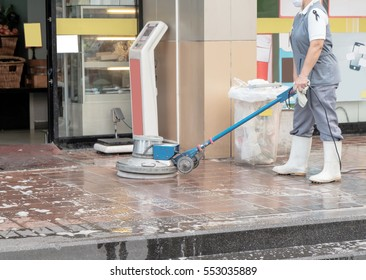 Worker cleaning floor with scrubber machine. Movement.