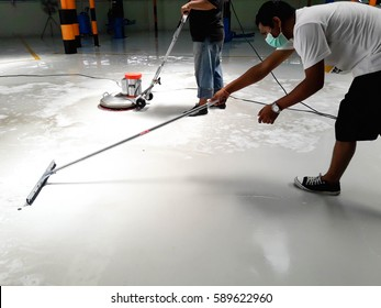 worker cleaning floor with scrubber machine