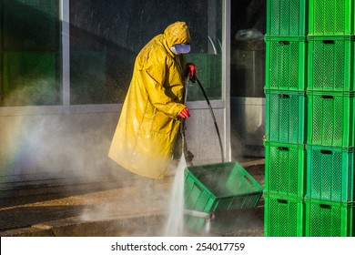 Worker cleaning green boxes in yellow safety protective equipment