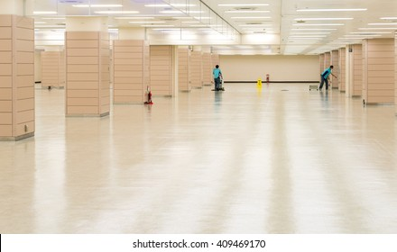 Worker cleaning hall floor of office building