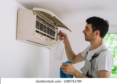 worker cleaning home air conditioner with antibacterial spray