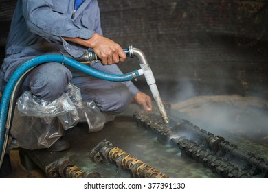 Worker is cleaning the machine equipment by using the air pressure sand / dryice blasting