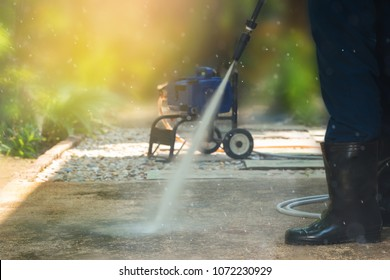 Worker cleaning pathway with high pressure washer splashing the dirt,low angle view backlighting. High pressure cleaning,lower body with waterproof boots.Professional cleaning services.