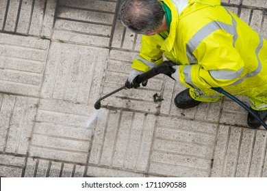 Worker cleaning the sidewalk with pressurized water. Maintenance or cleaning concept. Top view