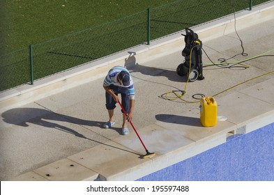 A worker is cleaning a swimming pool with a brush