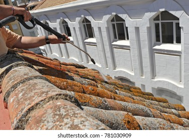 Worker cleaning a traditional tiles roof with high pressure water jet, Seville, Spain