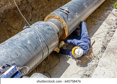 Worker is cleaning welding seam on pipeline with a grinding machine. Preparation for welding
