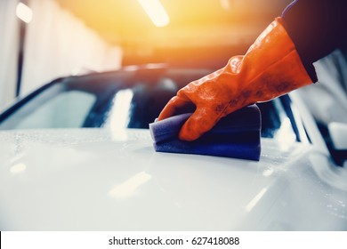 Worker cleaning white car. Concept manual car wash for cars.