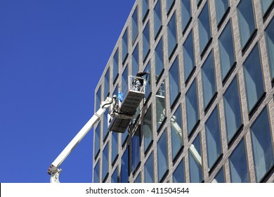 Worker cleaning windows service on building
